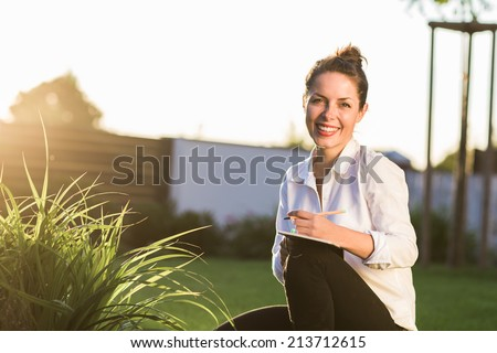 Young happy businesswoman or landscape architect sitting in the garden with her notebook. Young professional smiling at camera and dressed in casual clothes. Strong sunset backlit. Copy space. - stock photo