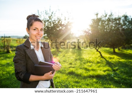 Young happy businesswoman or landscape architect standing in field, park or garden with her tablet. Young professional smiling at camera dressed in casual clothes. Strong sunset backlit. - stock photo