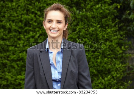 young happy businesswoman, outdoor shoot, blurred hedge behind her, can be used as copy space - stock photo