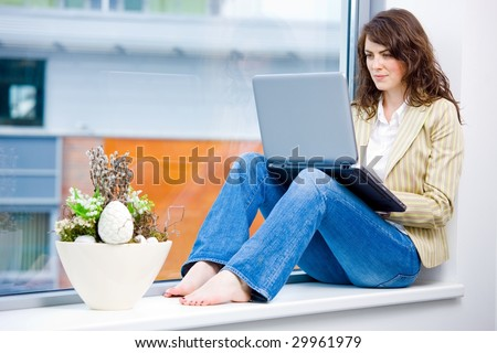 Young happy businesswoman sitting in office window and wokring on laptop computer, smiling. - stock photo