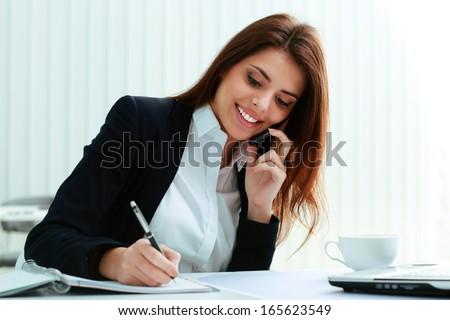 Young happy businesswoman talking on the phone and writing notes in office - stock photo