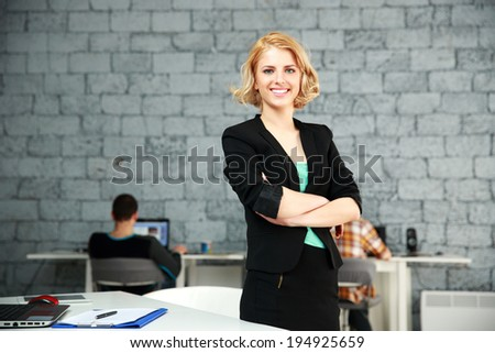 Young happy businesswoman with arms folded standing in office - stock photo