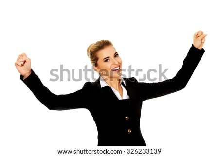 Young happy businesswoman with arms up. Winning concept. - stock photo