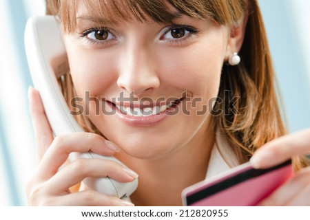 Young happy businesswoman with phone and plastic or credit card, at office - stock photo