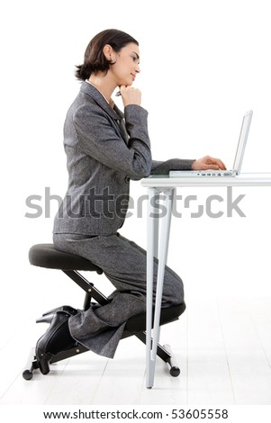 Young happy businesswoman working on kneeling chair, smiling, isolated on white. - stock photo