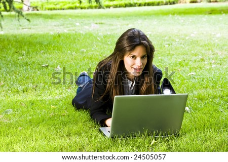 Young happy businesswoman working on the grass