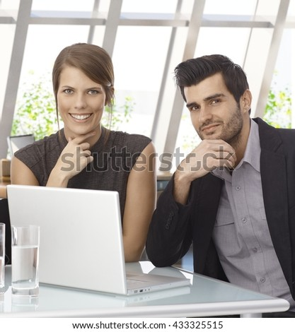 Young happy caucasian businessman and businesswoman with laptop computer. Sitting at office table, looking at camera, hand under chin, smiling.