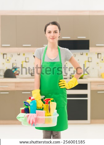 young happy caucasian female standing in kitchen holding cleaning products - stock photo