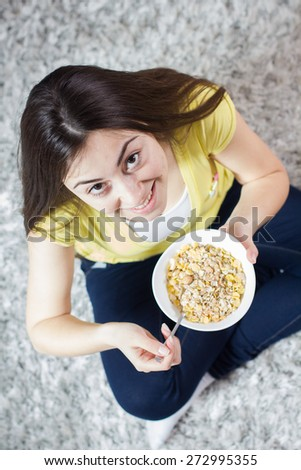 Young Happy Caucasian Woman Eating Cereal Muesli for breakfast. - stock photo