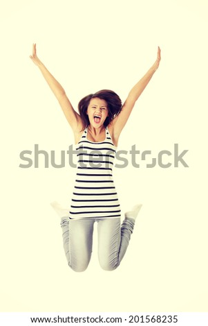 Young happy caucasian woman jumping in the air.