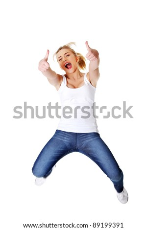 Young happy caucasian woman jumping in the air with thumbs up , isolated on white background - stock photo
