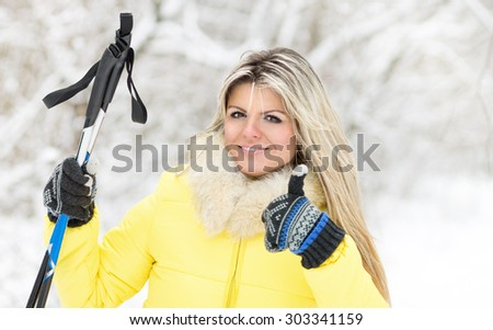Young happy caucasian woman with ski poles at winter skiing outdoor. Pretty blond girl with thumb up  - stock photo