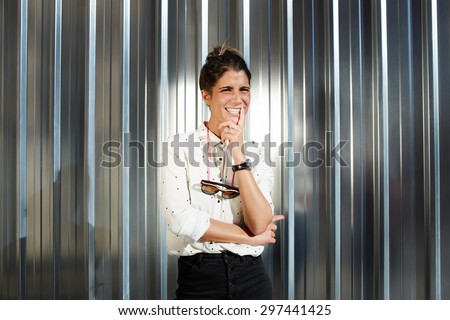 Young happy cheerful woman sincerely smile or laugh while posing for the camera on a sunny day, hipster standing on shiny chrome background with copy space for your text message or advertising content - stock photo