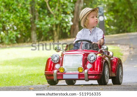 young happy child boy driving a toy car outdoors in park