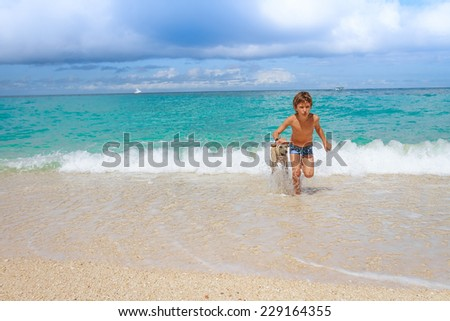 young happy child boy having fun with white dog in the sea, summer vacation - stock photo