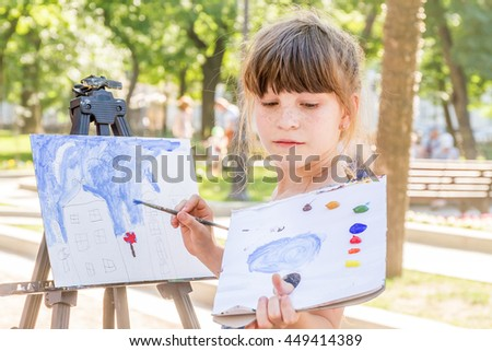 young happy child girl drawing a picture outdoors, kid painting - stock photo