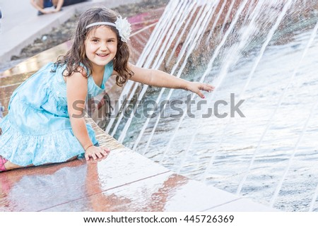 young happy child girl playing with water fountain, outdoor portrait - stock photo