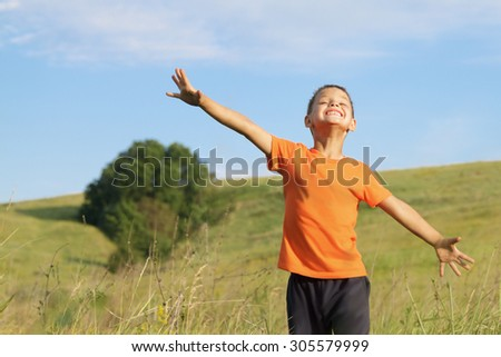 Young happy child play in  meadow.Freedom concept. - stock photo