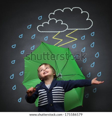 Young happy child singing and dancing holding an umbrella standing in front of a chalk drawing of a rain and lightning storm on a school blackboard - stock photo