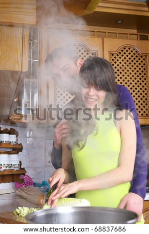 Young happy couple are cooking at home kitchen - stock photo