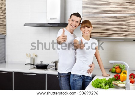 Young happy couple at kitchen - stock photo