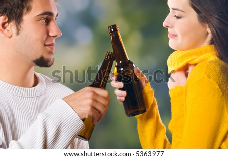 Young happy couple celebrating with beer outdoors - stock photo