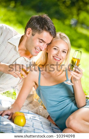 Young happy couple celebrating with champagne at picnic