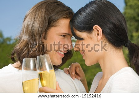 Young happy couple celebrating with champagne outdoors