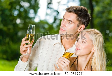 Young happy couple celebrating with champagne outdoors. Love, flirt, romantic, relations, celebration theme concept.