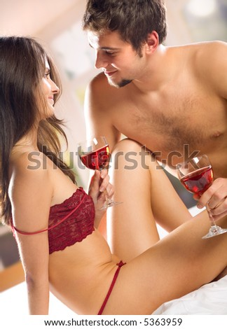 Young happy couple celebrating with red wine at bedroom - stock photo