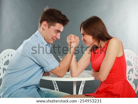 Young happy couple challenge fighting in arm-wrestling at table, in studio isolated on gray - stock photo