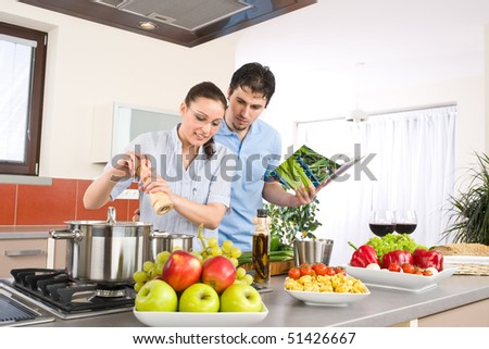Young happy couple cook in kitchen with cookbook, pasta, vegetable - stock photo