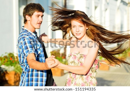 Young happy couple dancing on street outdoors - stock photo