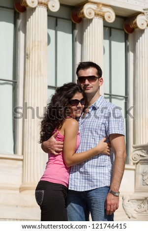 Young happy couple do sightseeing in Greek capital - city of Athens in a bright sunny day
