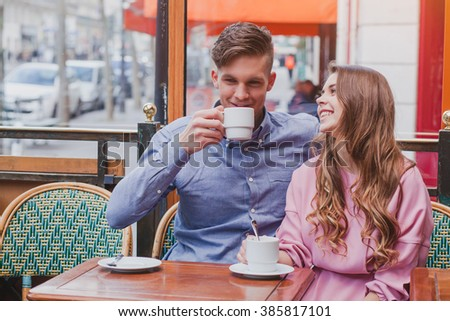 young happy couple drinking coffee and laughing in cafe in Europe, dating, good positive moments - stock photo
