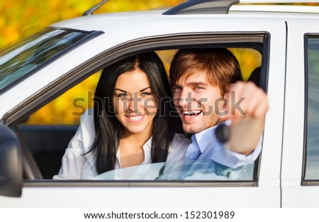 young happy couple driving, excited man and woman buy new car smile hold hand keys  - stock photo