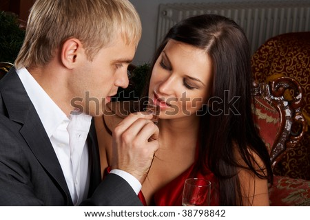Young happy couple eating chocolate at celebration