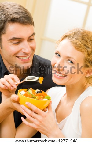 Young happy couple eating salad at home together