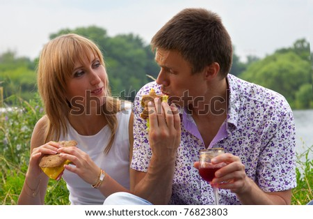 Young happy couple eating together outdoors - stock photo