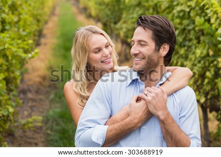 Young happy couple embracing each other in the grape fields - stock photo