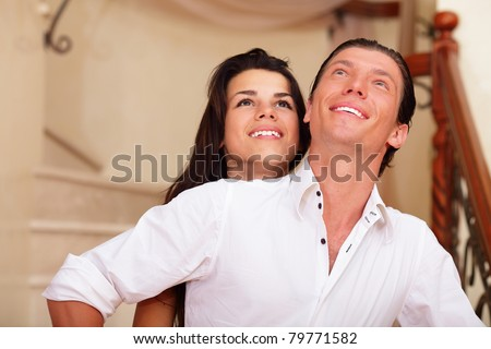 Young happy couple embracing in an new house and looking up - stock photo