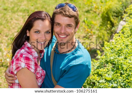 Young happy couple embracing in sunny park smiling pure romance - stock photo