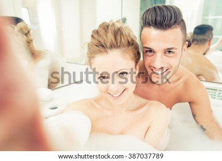 Young happy couple enjoying jot bath in the jacuzzi. taking a selfie in the jacuzzi - stock photo