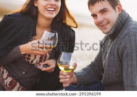 Young happy couple enjoying picnic with white wine on the beach together. Close up.Very noisy. Twilight time