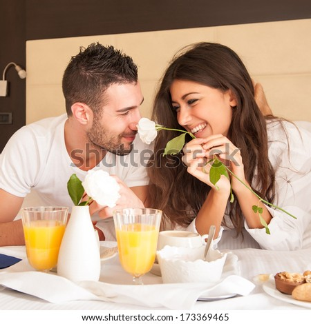 Young happy couple having breakfast in luxury hotel room.  - stock photo