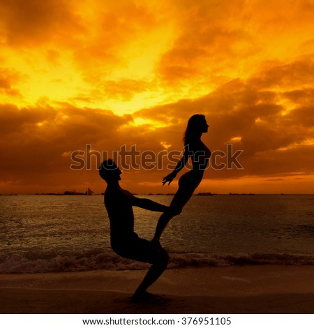 young happy couple having fun on a tropical beach with the sunset in the background