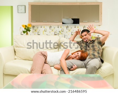 young happy couple having fun, sitting on sofa in living room