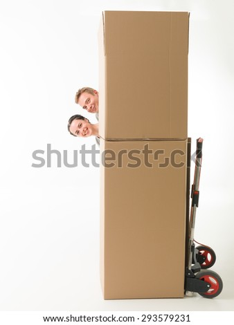 young happy couple hiding behind moving boxes, having fun. on white background - stock photo