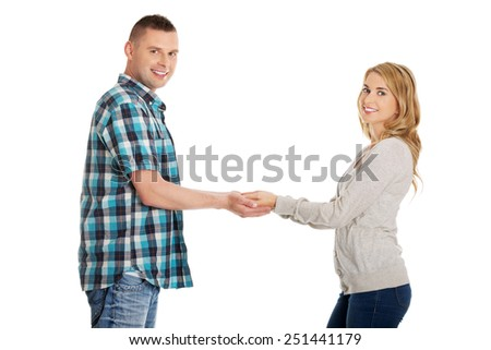 Young happy couple holding hands - stock photo