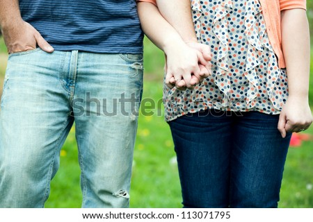 Young happy couple holding hands show at waist height showing their jeans and the womans diamond engagement ring. - stock photo